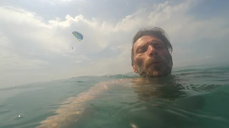 POV of man with beard swimming in sea water on sunny day Paragliding on background Summertime