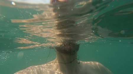 POV Man spits sea water to action camera Summertime Wideo