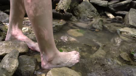 çekicilik : Close up of womans legs walking barefoot in mountain river in forest