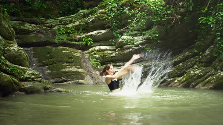 cercar : Young beautiful woman splashes on water by hands in small mountain lake in green tropical forest