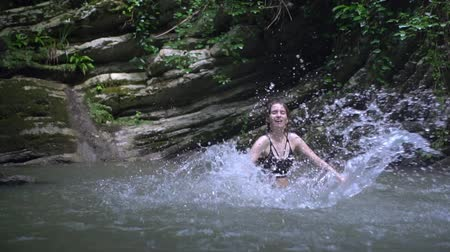 cercar : Slow Motion Young beautiful woman splashes on water by hands in small mountain lake in green tropical forest