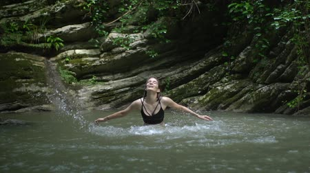 cercar : Slow Motion Young beautiful woman splashes on water by hands in small mountain lake near waterfall in green tropical forest