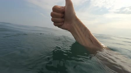 şeklinde : Male hands showing Valentines Day heart, ok, thumb up hand sign gesture. Male hands with heart shaped fingers. Man making the symbol of love with hands. Gestures and signs. Body language on blue sea water background Closeup POV Point of view