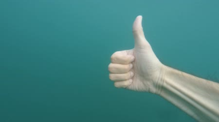taça : Male hand showing thumb up and ok sign gesture on blue underwater background with bubbles. Gestures and signs. Body language on blue sea water background Closeup POV Point of view