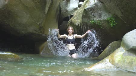 pedregoso : Slow Motion beautiful girl splashes on water by hands in mountain lake in green tropical forest with waterfall, boulders and moss on background in jungle natural park in mountains Stock Footage