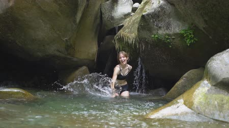 stony : Slow Motion beautiful girl splashes on water by hands in mountain river in green tropical forest with waterfall, boulders and moss on background in jungle natural park in mountains