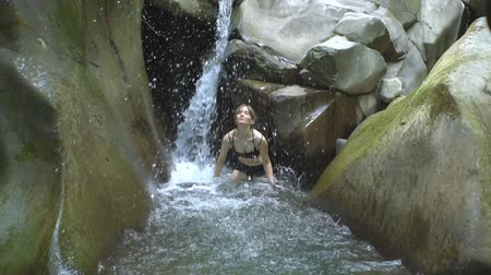 boulders : Beautiful girl in slow motion splashing clear water of mountain lake and looks to camera with small waterfall in green tropical forest with boulders and moss on background in jungle natural park Stock Footage