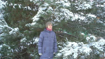 Финляндия : Attractive woman posing on background of pine with snow in her winter garden for Merry Christmas and Happy New Year