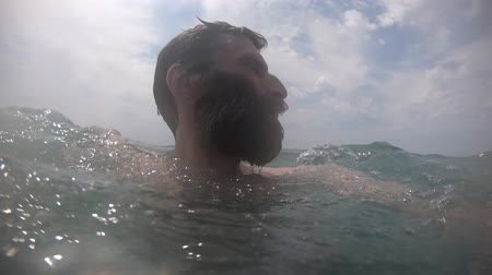 Man hardly swims in sea water with waves at sunny day POV 動画素材