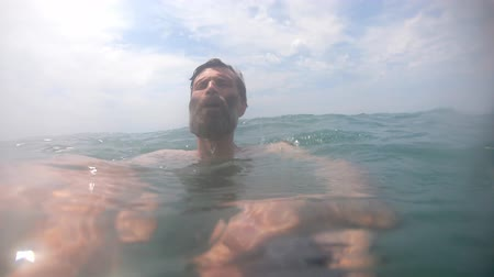 Man hardly swimming in sea water with waves at sunny day POV Wideo