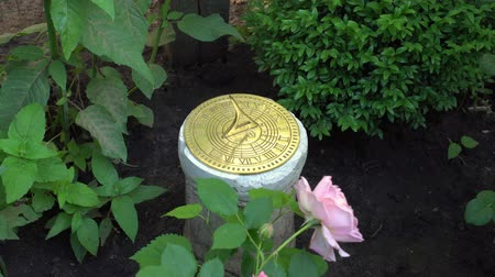 Close up of sundial in an English garden on background of roses