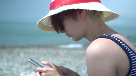 Young beautiful hipster woman using smartphone wearing retro hat and swimsuit with blue and white stripes in lonely summer beach. Internet surfing