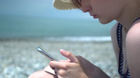 Pretty young woman using smartphone by the sea beach. Girl in retro hat and swimsuit with blue and white stripes. Technology and rest concept. Wideo