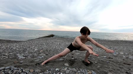 Young beautiful woman doing stretching exercise at seashore. Healthy lifestyle. Fitness concept. 動画素材