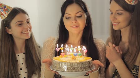 beijos : Three pretty girls celebrate and applaud. Birthday girl blows out the candles on the cake Full HD 1080 NTSC