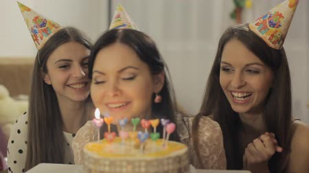aprósütemény : Three pretty girls celebrate and applaud. Birthday girl blows out the candles on the cake Full HD 1080 NTSC