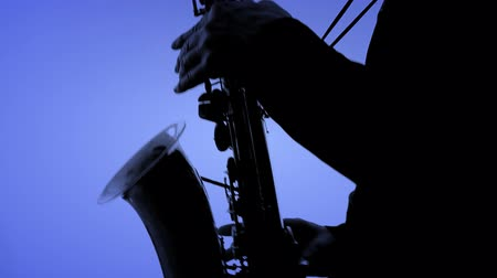 saxofone : Man playing sax in silhouette.  NTSC. You can change the background color using the tool HSL