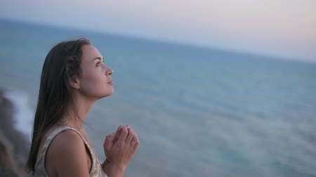 bondade : Sad happy girl prays at sunset by the sea Stock Footage