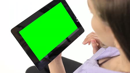 aluno : Girl sitting and working with the tablet on white. GreenScreen