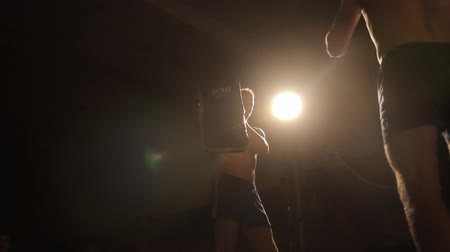tajlandia : Two strong boxers are training in the gymnasium. One of them holds the punching bag, another man kicks it in the backlight. Close-up and general plan HD 1080p 1920x1080 hidef definition