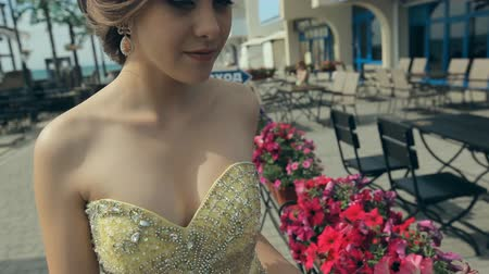 çekicilik : Cute young women in lemony long strapless dress touch bright flowers