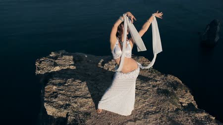 krym : Beautiful girl shows all the beauty of oriental dance standing on a mountain in Crimea Wideo