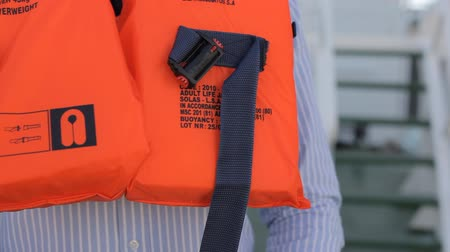 yelek : Man with black hair shows how to put on a lifejacket