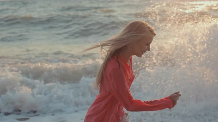 rusya : Young blond girl with long hair in red blouse on the beach