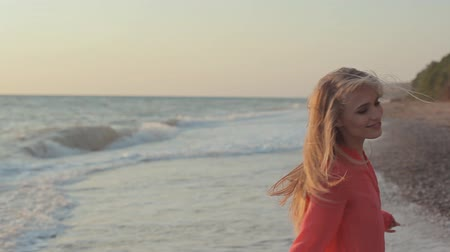 figuras : Young blond girl with long hair in red blouse on the beach