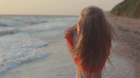 banhos de sol : Young blond girl with long hair in red blouse on the beach