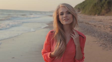 brisa : Young blond girl with long hair in red blouse on the beach