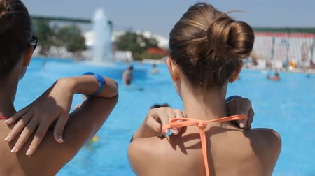 sıcak : Amazing beautiful young girls in bathing suits sitting and swimming in the pool Stok Video