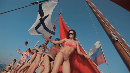 relaxační : Young girls in bikini relaxing on a yacht with red sails and a Russian flag