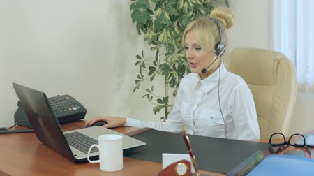 titkár : Attractive girl sitting in office with headphones and talking