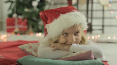 almofada : Adorable little girl blonde lies on the pillow in Santas hat