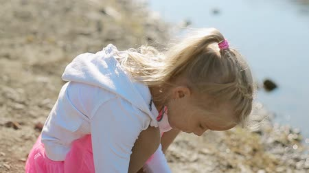babygirl : Little blond girl throwing stones into the water of the pond