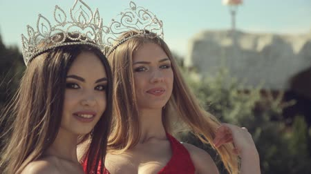 pózol : Two gorgeous girls with long hair and crown with jewels on the head smiling in garden