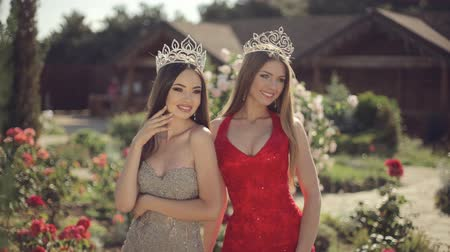 giydirmek : Two sexy young women posing in evening gowns and crowns in a beautiful garden Stok Video