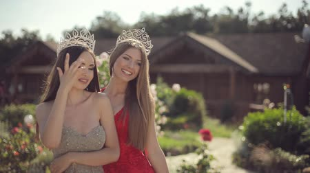 earings : Two amazing girls in a long gowns and crowns laughing in the park with roses Stock Footage