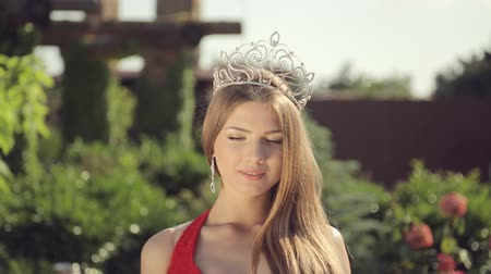 coroa : Beautiful girl with a crown and a slender figure walking in the garden with roses
