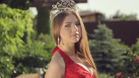 giydirmek : Tender girl with a beautiful figure in a long red dress and with a crown on her head walking in the garden with roses