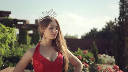 boldness : Portrait of a sexy young woman in a long red dress and a crown in the garden with roses