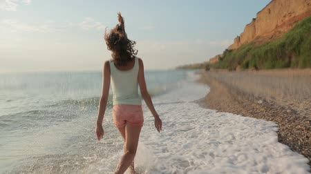 serbest : Free girl running barefoot on the water along a deserted beach in the summer
