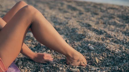 güneş ışını : Seductive girl sitting on the beach near the sea touching and throwing pebbles