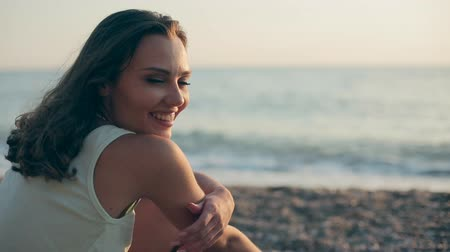 релаксация : Cheerful girl sitting near a sea and smiling