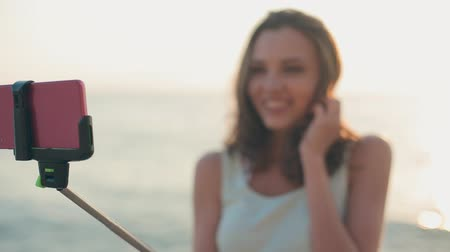vara : Attractive girl standing in the sea with a monopod and makes selfie to the phone