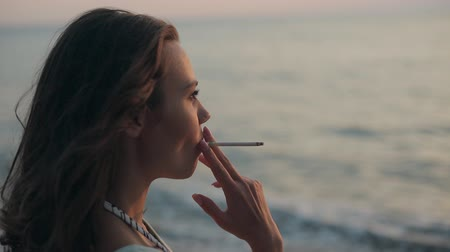 cigarettes : Girl smoking a cigarette at sunset near the sea