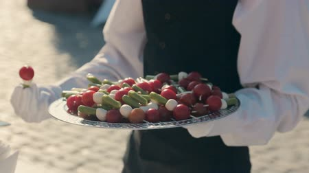 общественное питание : Waiter puts canape with cherry tomatoes and cheese on a plate on catering