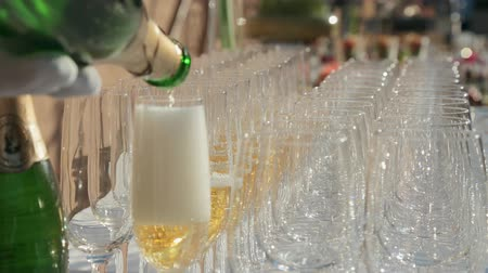 сверкающий : Waiter fills empty glasses with champagne at a banquet
