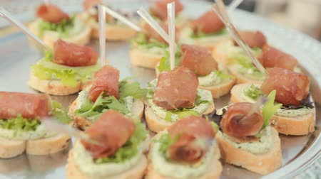 sandviç : Sandwiches with cream cheese, leaf of lettuce and a piece of ham on catering Stok Video
